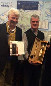 Speyside Distillery CEO John Harvey McDonough (left) presents successful bidder James Robertson with bottle number one from Cask 27